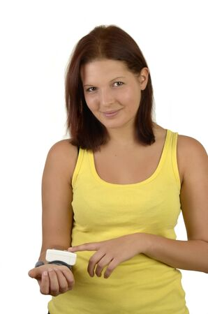 Young sporty woman in a yellow tank top controls blood sugar levels on the meter and smiles, portrait format, isolated on whte background