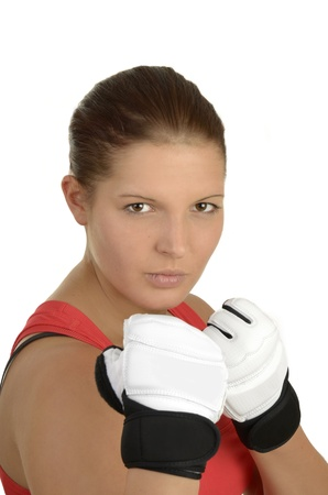 Young beautiful sportswoman in a red top with kick boxing gloves and a determined look in front of white background, portrait studio shot photo