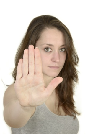 self confident: young woman shows open hand before white background, idolated, studio shot