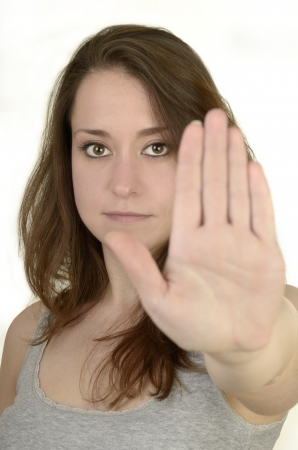 young woman shows open hand before white background, idolated, studio shot photo