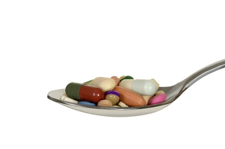 spoon with colorful different pills, isolated, white background, studio shot photo