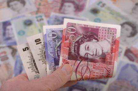 sterlina: mano tiene British Pounds banconote, girato in studio Archivio Fotografico