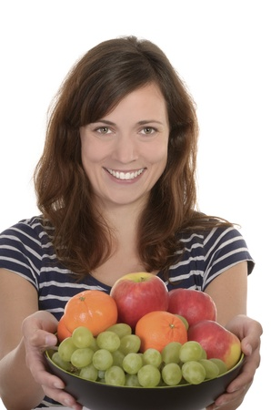 Happy young woman holding bowl of fresh fruits, studio shot, isolated Stock Photo