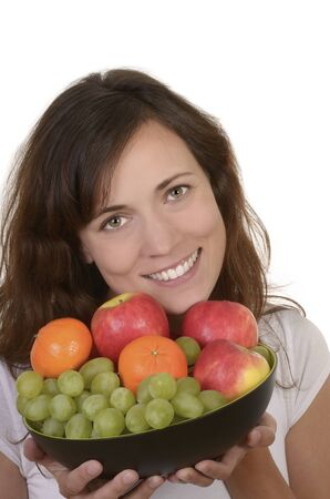 Happy young woman holding bowl of fresh fruits, studio shot, isolated, copy space photo