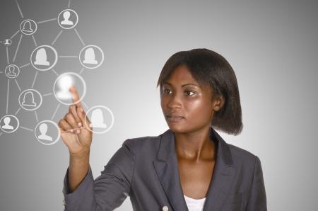 African business woman touching virtual touchscreen, studio shot photo