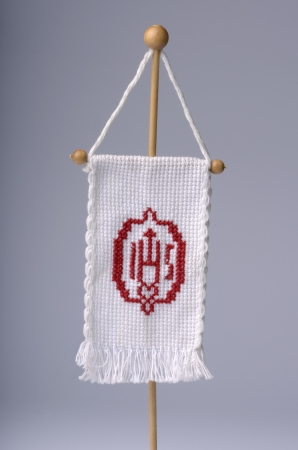 liturgy: IHS monogram on embroidered flag, grey background, studio shot