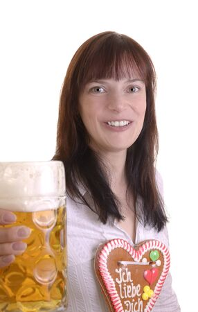 consumerist: Young woman with beer jug and gingerbread heart, studio shot Stock Photo