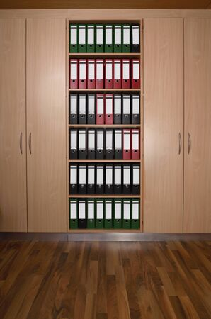 file cabinet: Office cupboard with different folders, wooden floor
