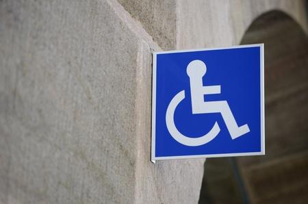 handicap: Wheelchair sign on wall in urban context