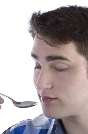 closed eye: Young man in blue shirt is smelling spoon, Studio Shot