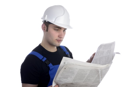 social worker: Young construction worker studying newspaper for jobs