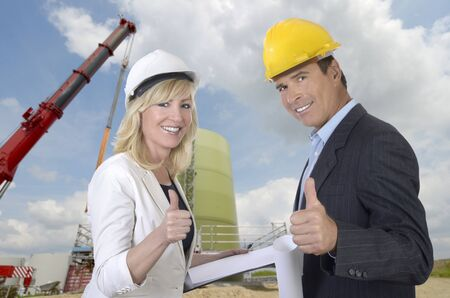Male and female architect and construction site smiling and thumb up, outdoor photo