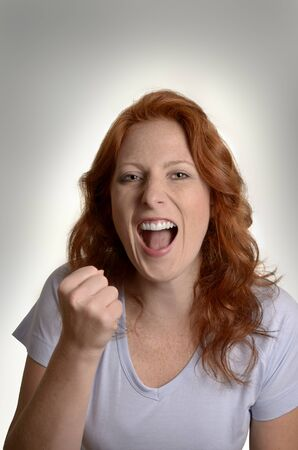 Pretty red-haired woman jubilating, Studio Shot photo