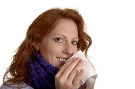 Pretty red-haired is cleaning her nose, Studio Shot Stock Photo - 22479238