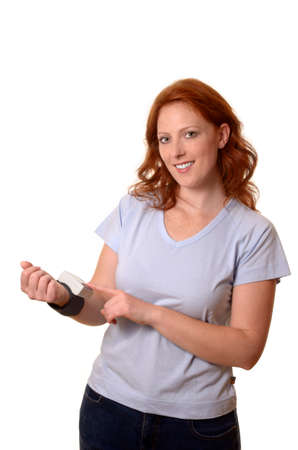 Pretty red-haired woman controlling blood pressure, Studio Shot photo