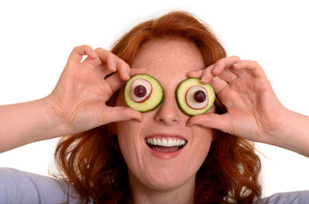 fooling: Pretty red-haired woman fooling around with vegetables, Studio Shot Stock Photo