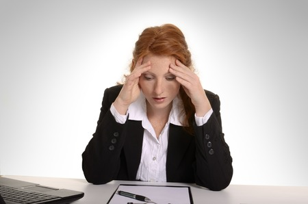 Pretty red-haired business woman suffering burn out, Studio Shot