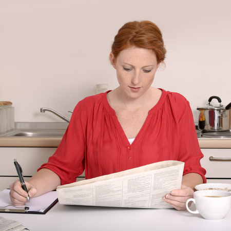 Pretty red-haired woman searching for job, Studio Shot
