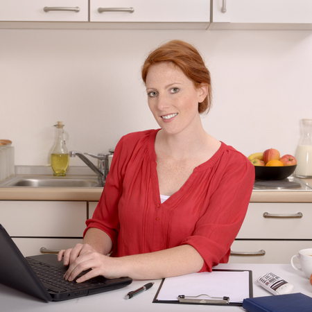 self contained: Pretty red-haired woman working in her home office, Studio Shot Stock Photo