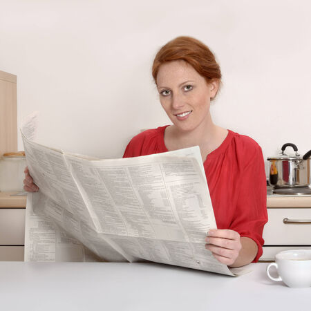 Pretty red haired woman reading newspaper, Studio Shot