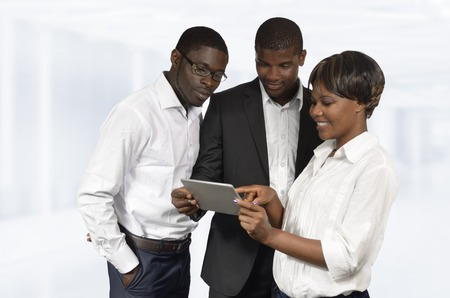 African Business People discussing with Tablet PC, Studio Shot