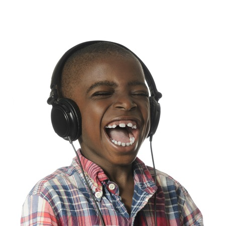 male child: African boy with headphones listening to music, Studio Shot