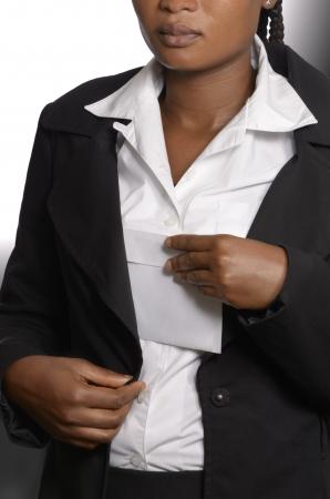 corrupcion: Mujer africana poniendo soborno en la chaqueta, Foto de estudio