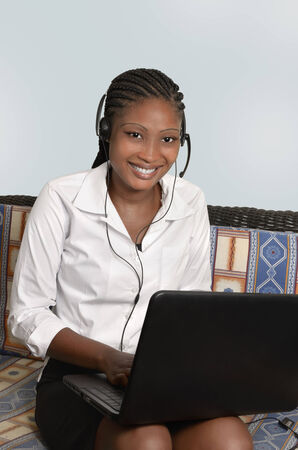 African woman with notebook and headset, Studio Shot photo