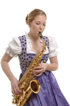 Woman in dirndl dress playing saxophone, Studio Shot photo