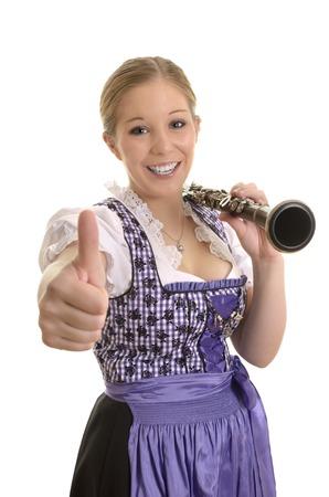 dirndl dress: Pretty woman in dirndl dress with saxophone, thumb up, Studio Shot Stock Photo