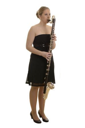 woodwind instrument: Pretty young woman playing bass clarinet, Studio Shot Stock Photo