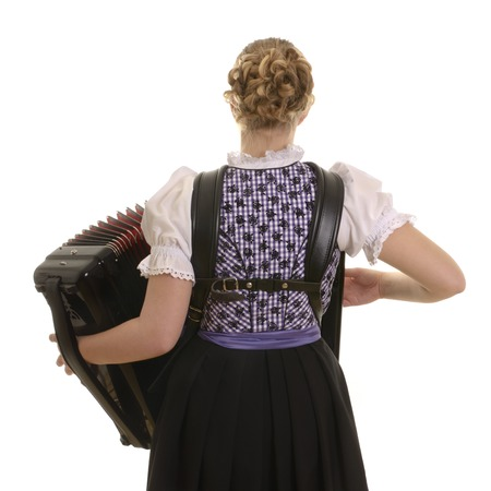 Rear view of young drindl woman playing accordion, Studio Shot photo