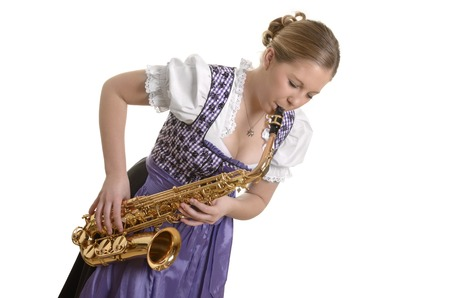dirndl dress: Woman in dirndl dress playing saxophone, Studio Shot