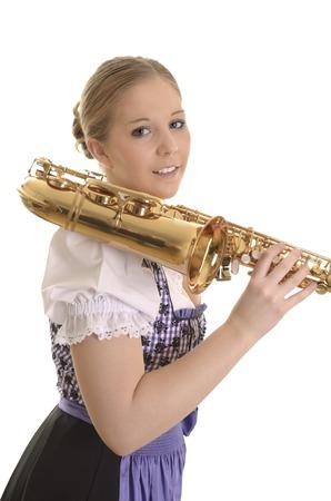 dirndl dress: Portrait of a woman in dirndl dress with saxophone, Studio Shot