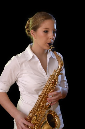 Pretty young woman playing saxophone, Studio Shot photo