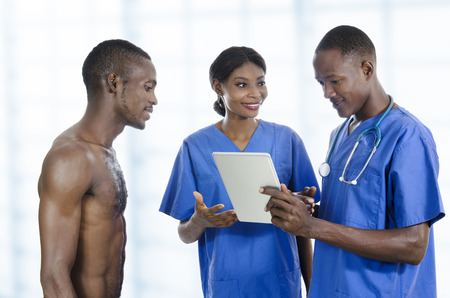 nursing unit: African health care team with tablet PC and patient, Studio Shot Stock Photo