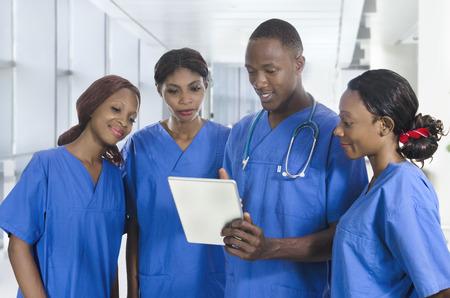 タブレット PC は、スタジオ撮影でアフリカの医師チーム 写真素材