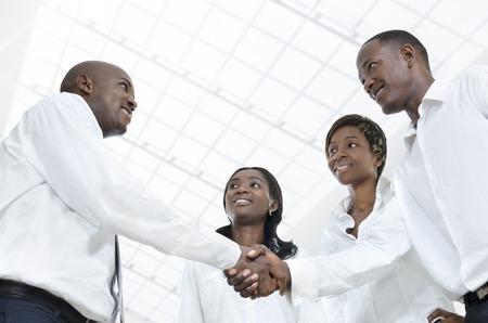 Vier afrikanische Geschäftspartner Hände schütteln, Studioaufnahme