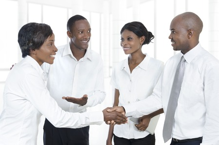 african american businesswoman: Four african business partners shake hands, Studio Shot
