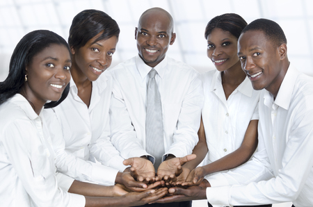 African business team presenting with open hands, Studio Shot Stock Photo