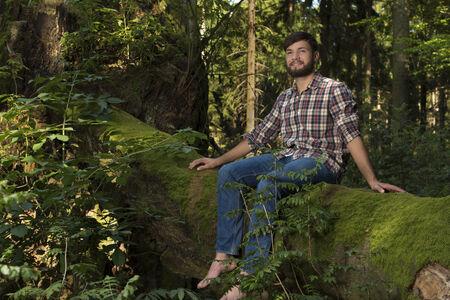 aventurero: Aventurero joven que se sienta en un tronco de disfrutar de la naturaleza, Toma exterior