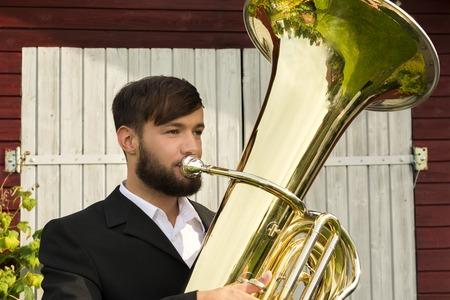 tuba: Male musician playing tuba, Outdoor Shot