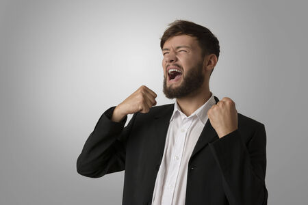 freak out: Angry man with clenched fists, studio shot Stock Photo
