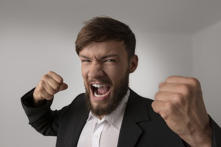 an outburst: Angry man with clenched fists, studio shot Stock Photo