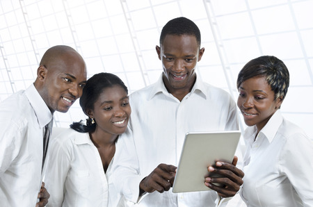 pcs: Four African business people with tablet PCs, studio shot Stock Photo