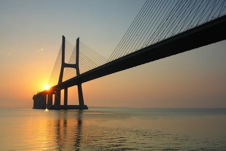 Sunrise and bridge over tagus river in Lisbon Portugal