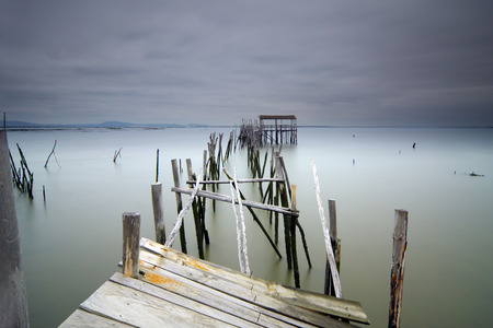 Remains of a wood pier in Carrasqueira Portugal Banco de Imagens - 85349604