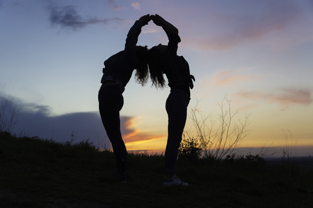 Silhouette of two women doing suryasana yoga posture at sunset