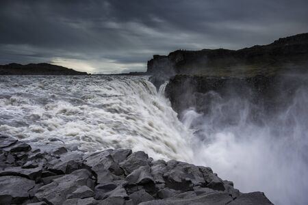On the edge of the powerful Dettifoss waterfall in Iceland