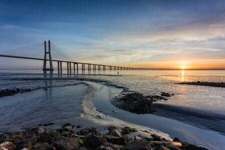 Vasco da Gama Bridge and pier over Tagus River in Lisbon, Portugal, at sunrise.